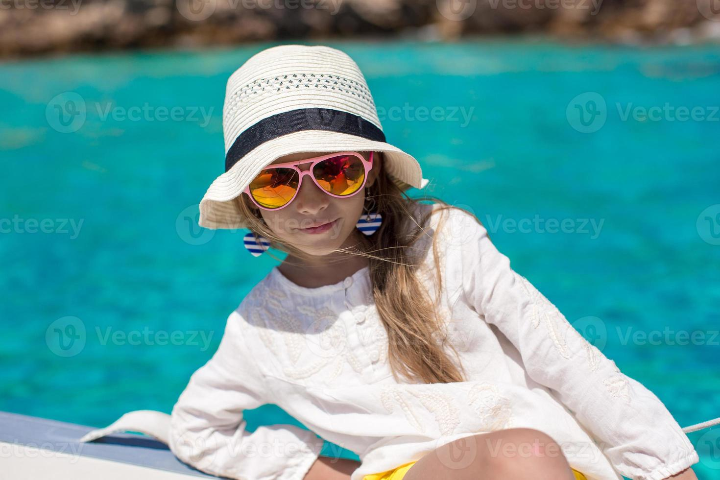 vacker liten flicka som tycker om att segla på båt i öppet hav foto