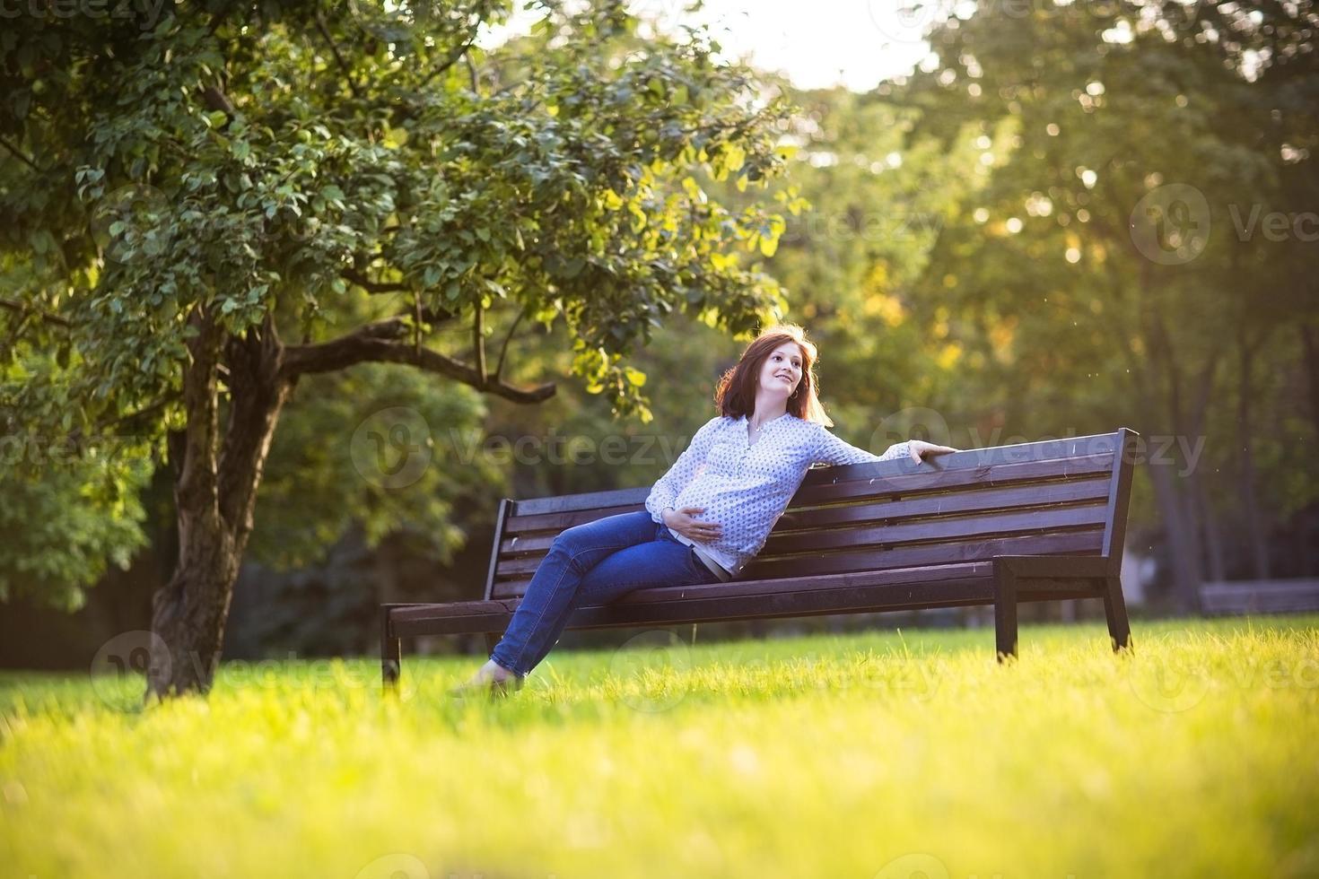 vacker ung gravid kvinna njuter av solnedgången i höst park foto