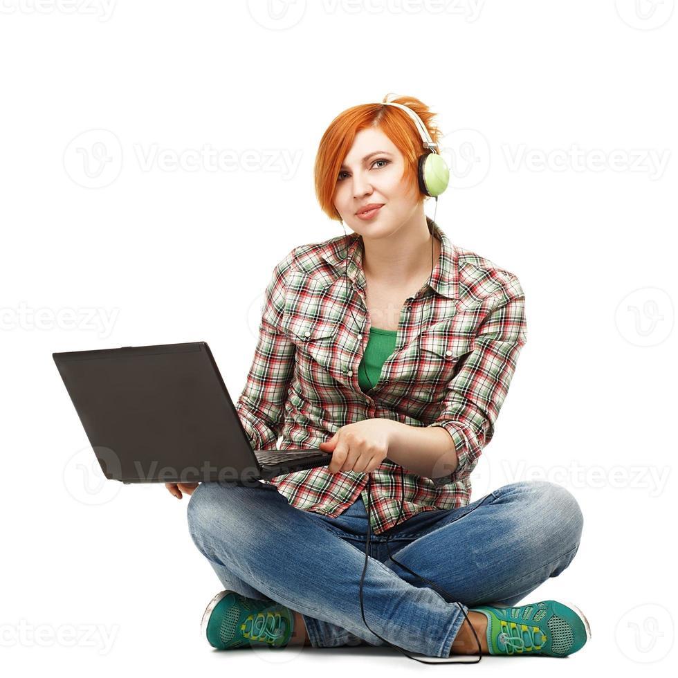 ung vacker flicka som tycker om att lyssna på musik i hörlurar i foto