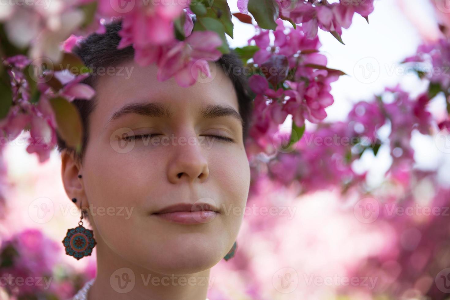 vacker flicka njuta av rosa blommande träd på sommaren foto