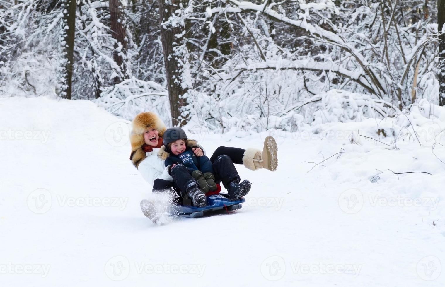 mamma och son njuter av släde på en vacker vinterdag foto