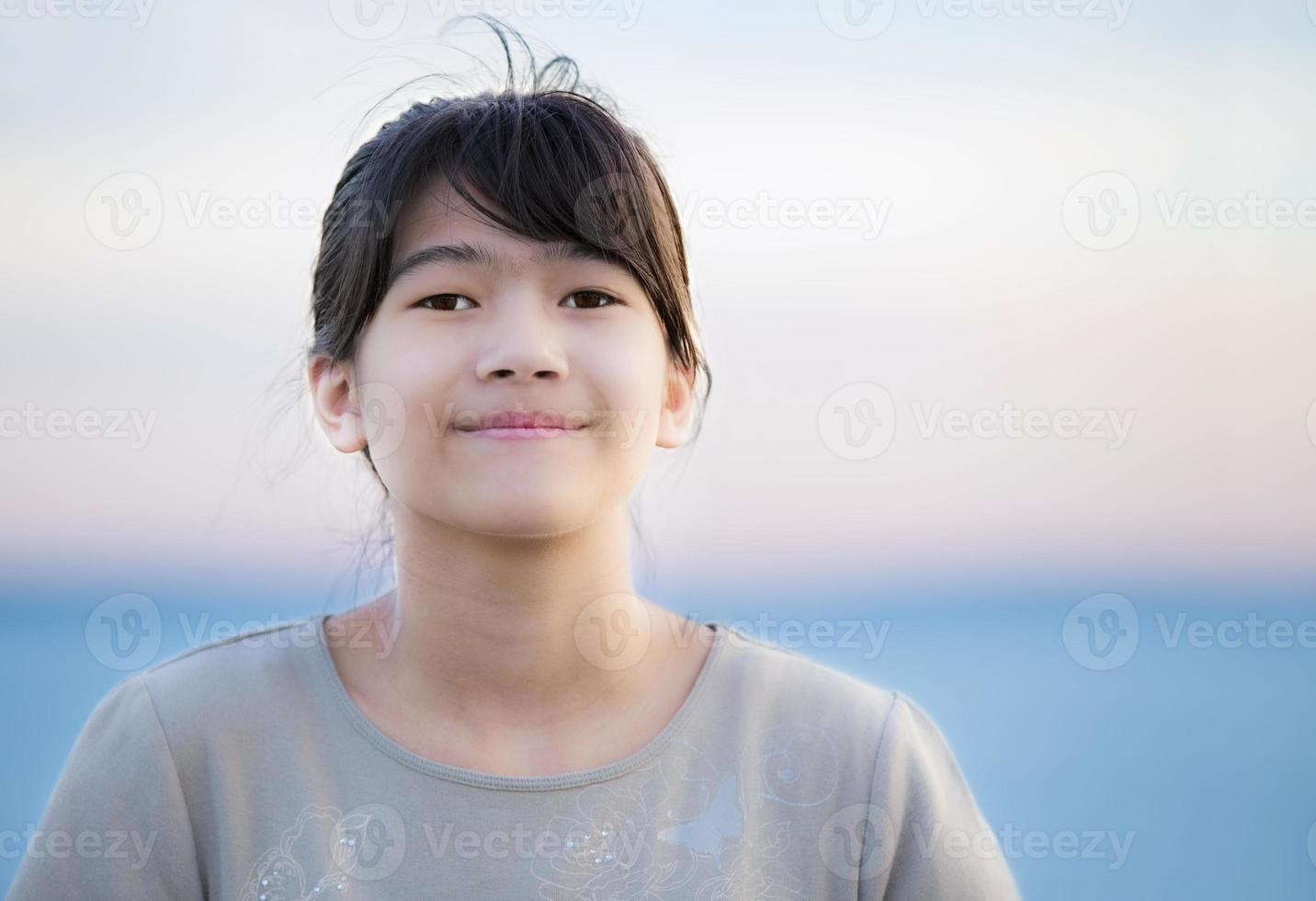 vacker ung preteen flicka njuter utomhus vid sjön vid solnedgången foto