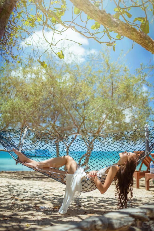 ung vacker kvinna som njuter av i hängmattan på havet foto