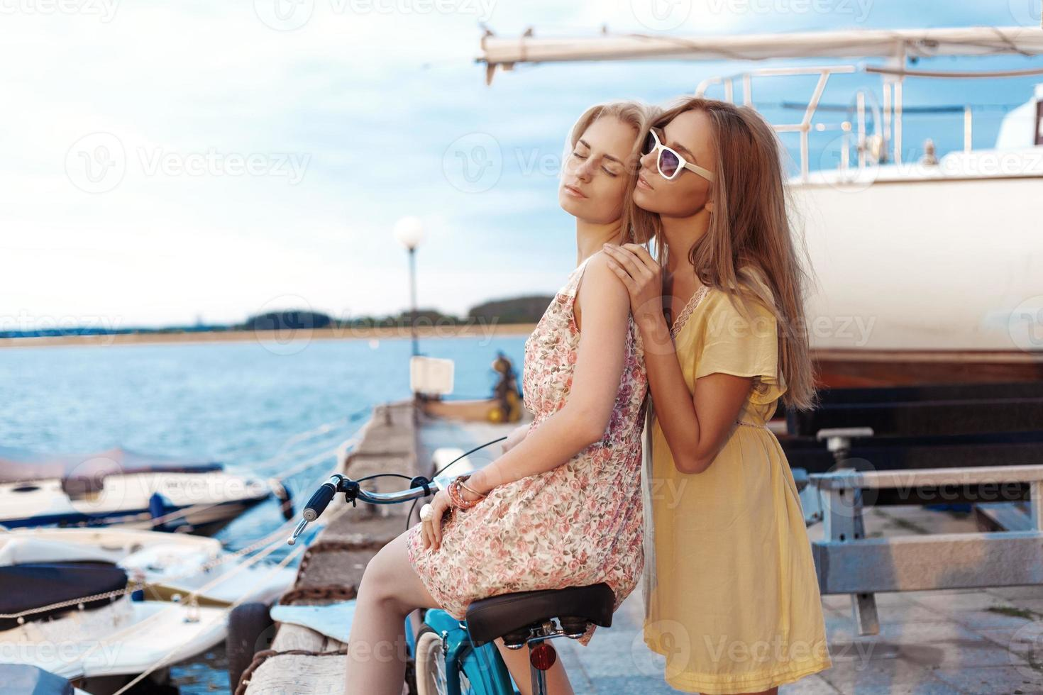två flickvänner som njuter av kvällssolnedgången i hamnen foto