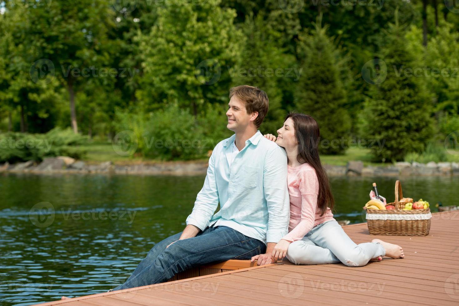 lyckliga romantiska par njuter av picknick i en park nära sjön foto
