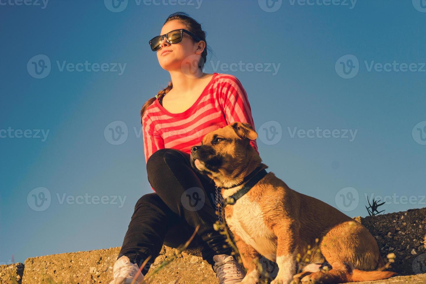 kvinna med en söt hund som njuter av en vacker dag utanför foto