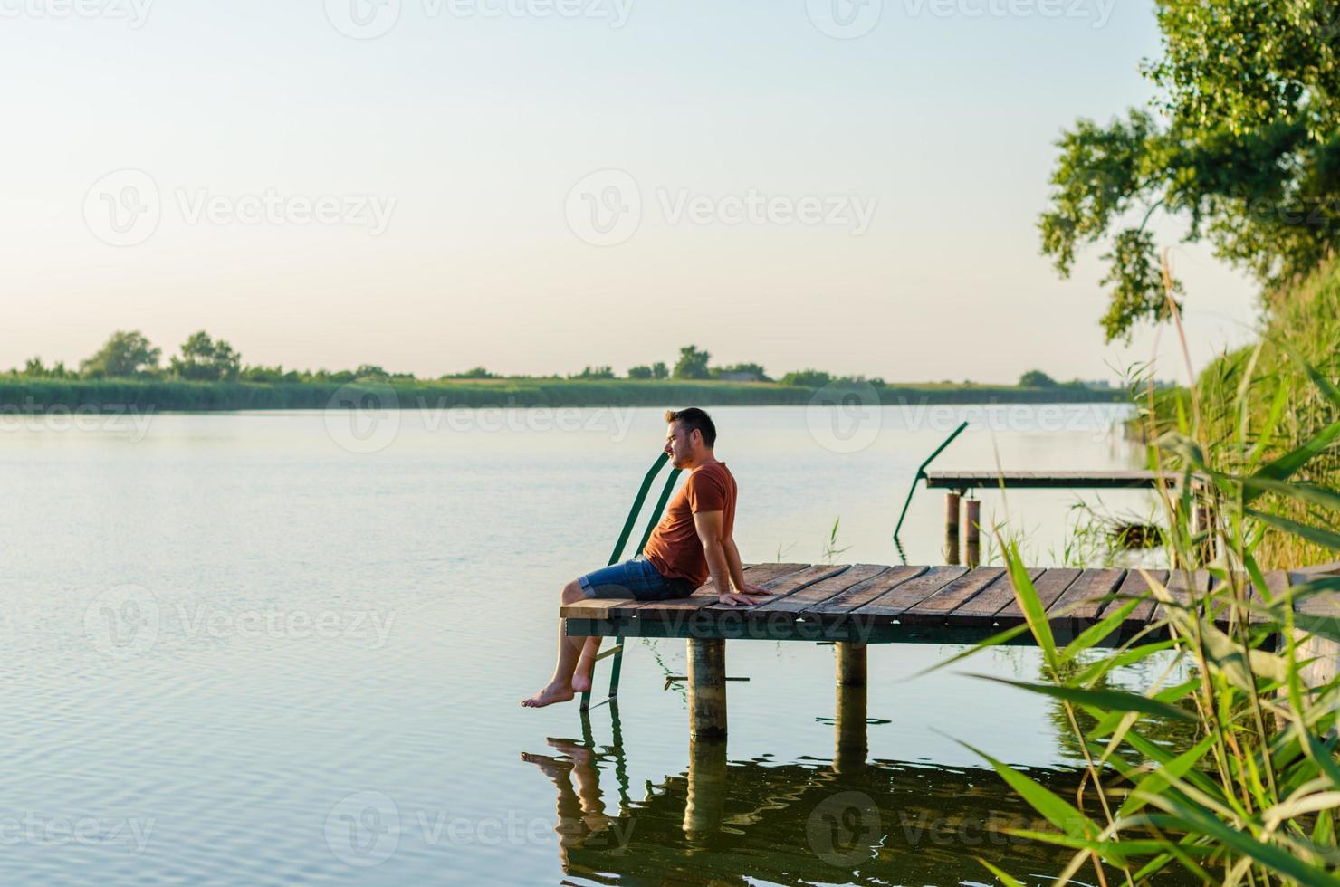 ung man sitter avkopplande och njuter av utsikten från kajen foto