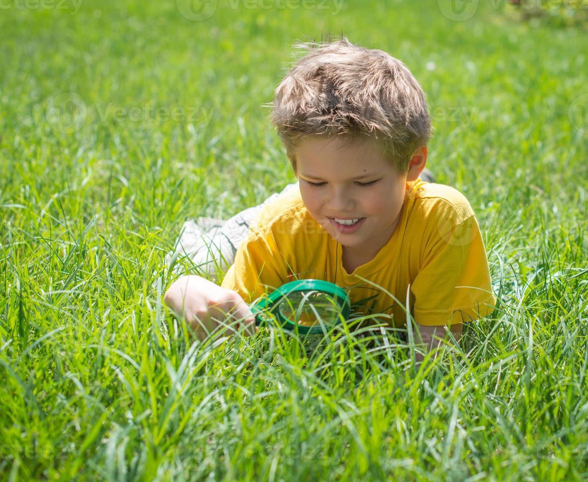 barn med förstoringsglas utomhus. glad pojke njuter av solig sommar. foto