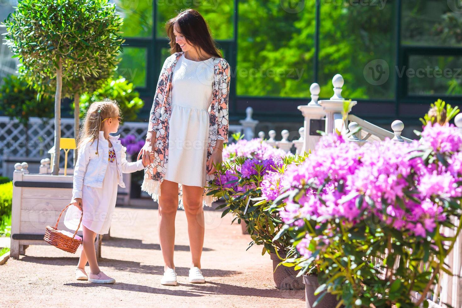 glad mamma och förtjusande tjej som tycker om varm dag i trädgården foto