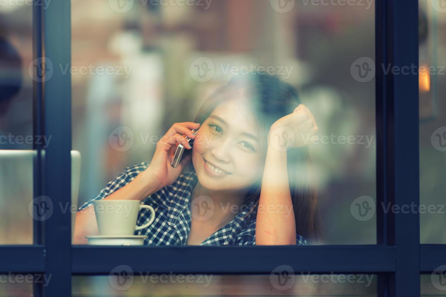 asien leende kvinna prata telefon på café och njuta av kaffe foto
