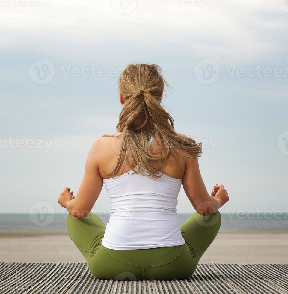 bakifrån ung kvinna i yogaställning på stranden foto