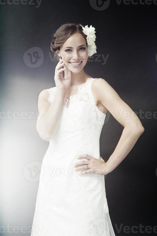 glamorös ung brud i bröllopsklänning, leende foto