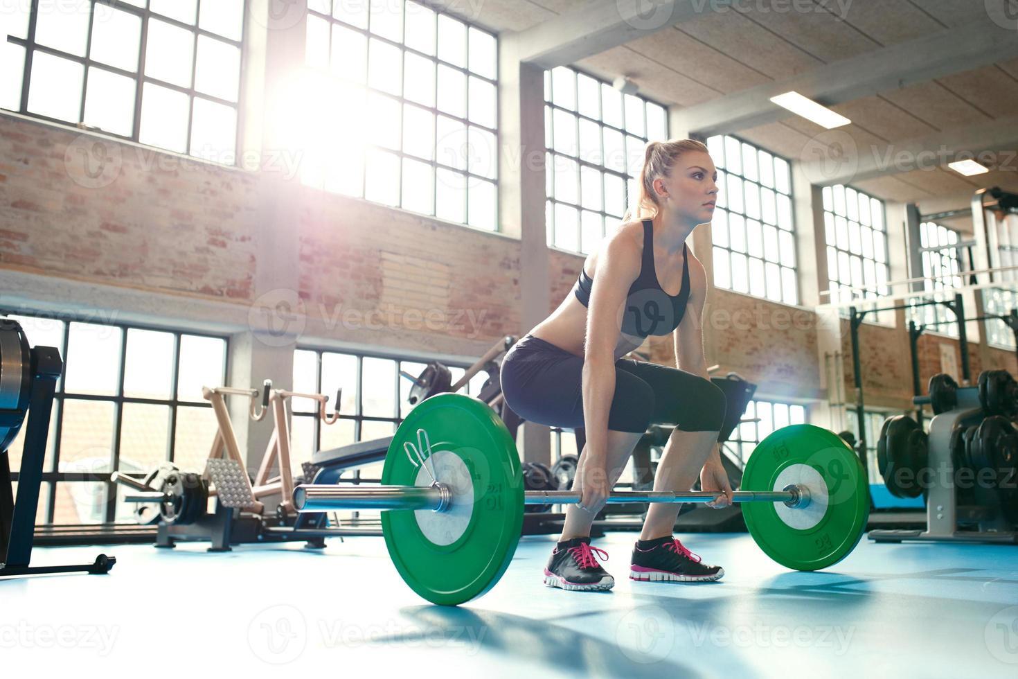 fokuserad ung kvinna som lyfter vikter i ett gym foto