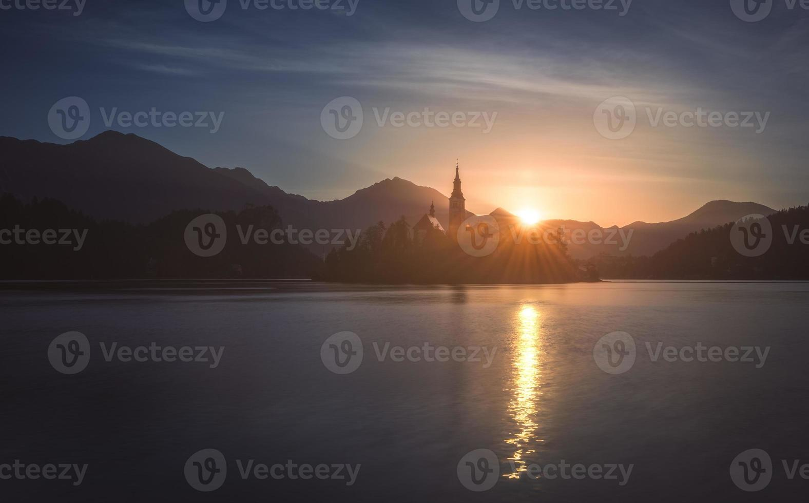 silhuett av den lilla ön med den katolska kyrkan i blödda sjön foto