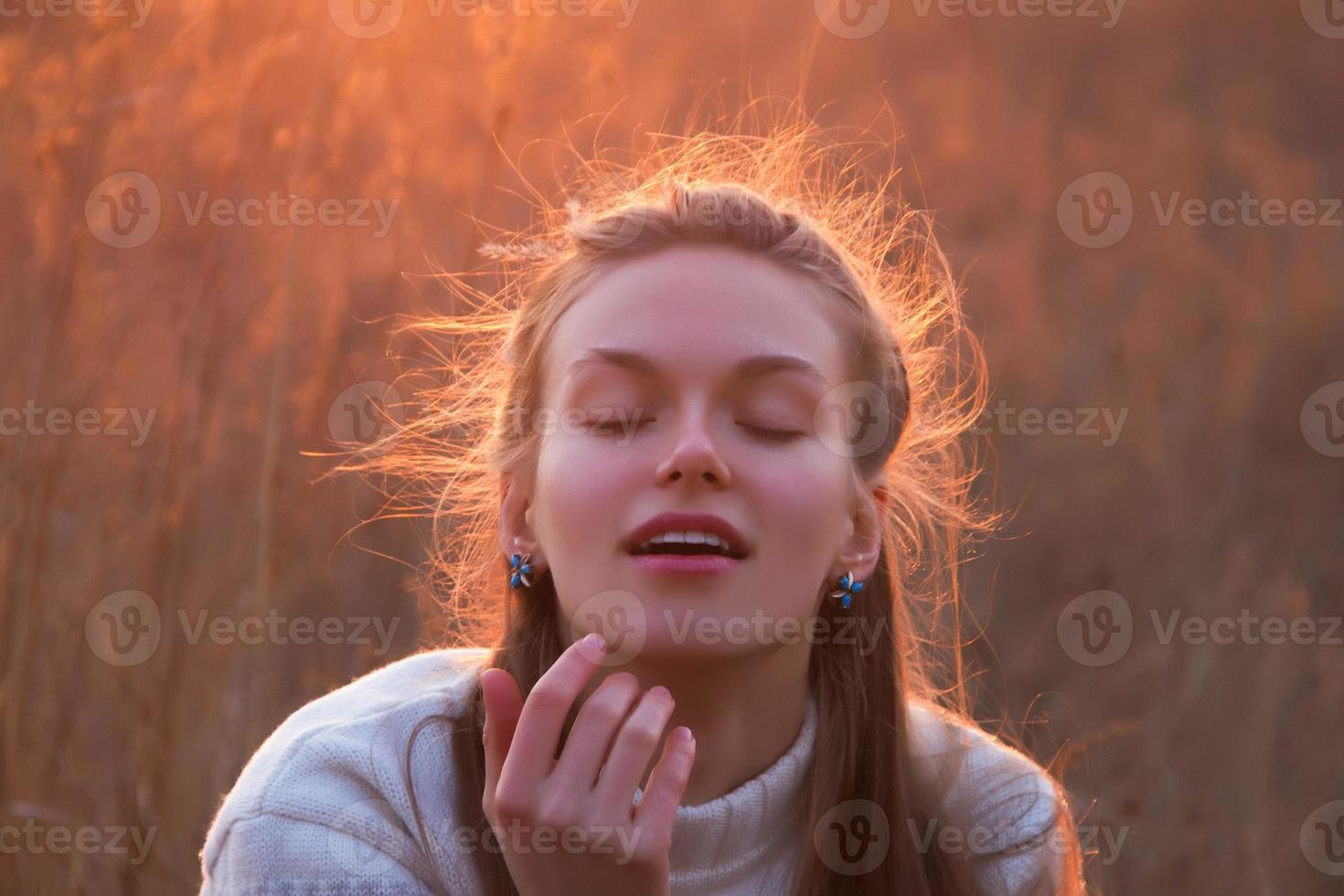 vacker ung blond kvinna dagdrömmar vid solnedgången foto