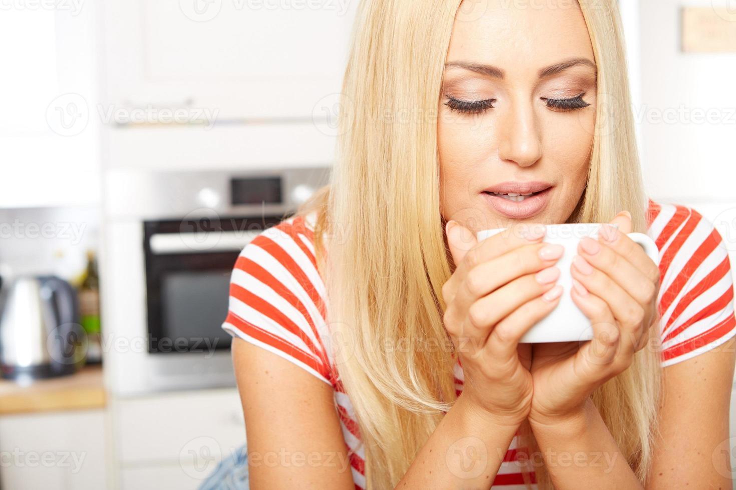 kvinna dricker kaffe på morgonen foto