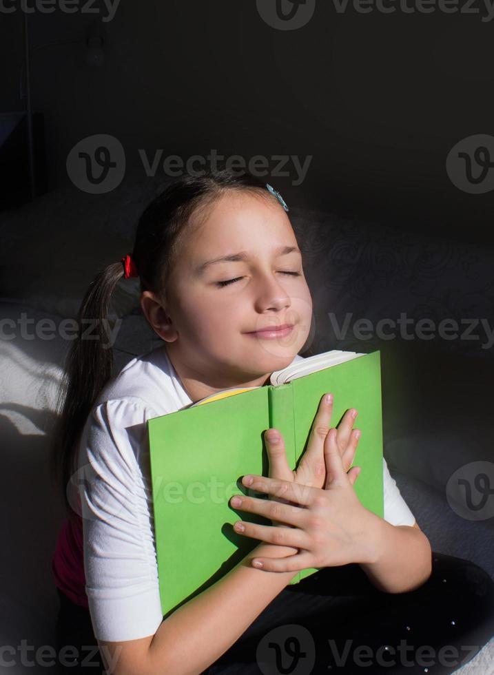 söt liten flicka med hästsvansar älskar sin bok inspirerad av hennes bok. foto