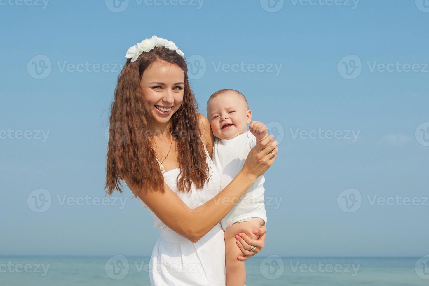 glad vacker mor och son njuter av stranden foto