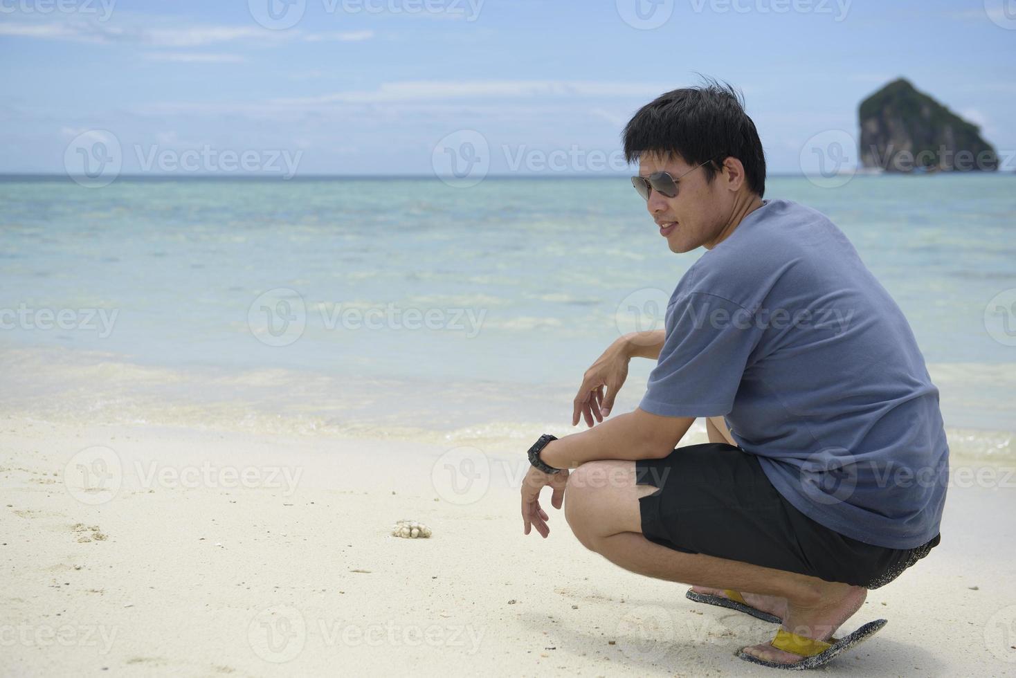 ung man njuter av tillflyktsort promenader längs stranden foto