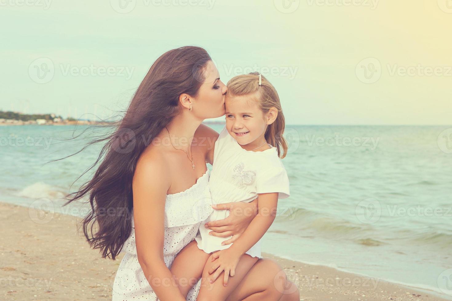 glad vacker mor och dotter som njuter av strandtid foto