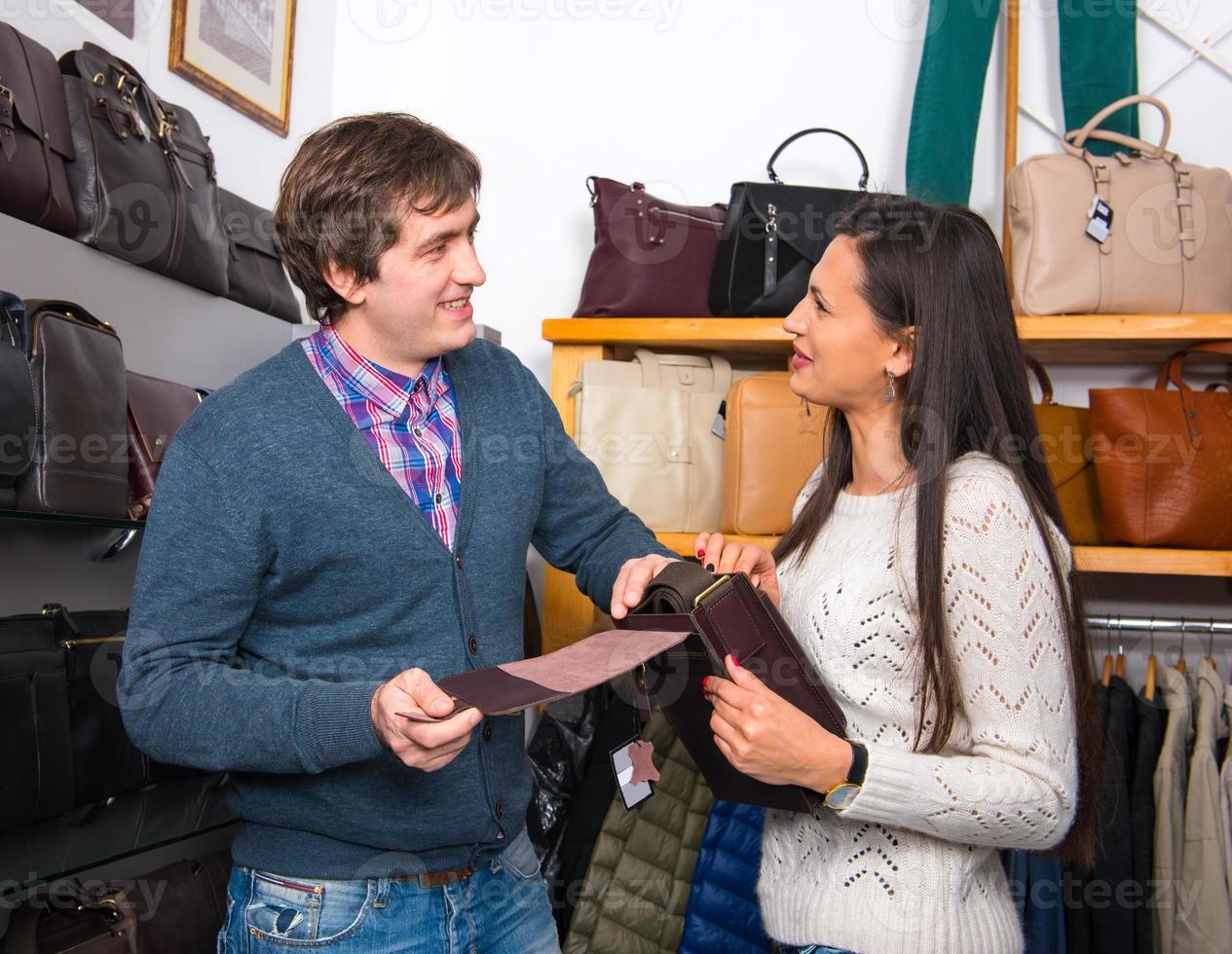 butiksassistent som visar läderväska till vacker kvinna foto