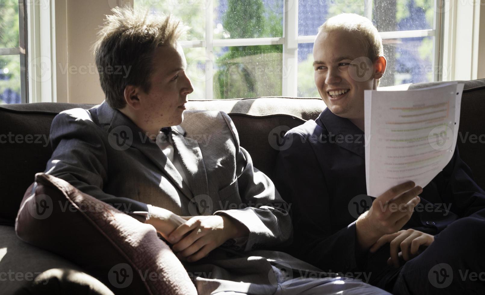 två unga vuxna som har kul under tiden förklarar de ett papper foto