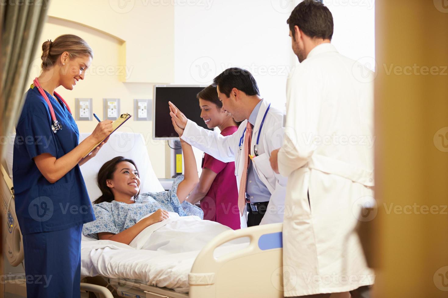 medicinskt teammöte runt kvinnlig patient på sjukhusrum foto