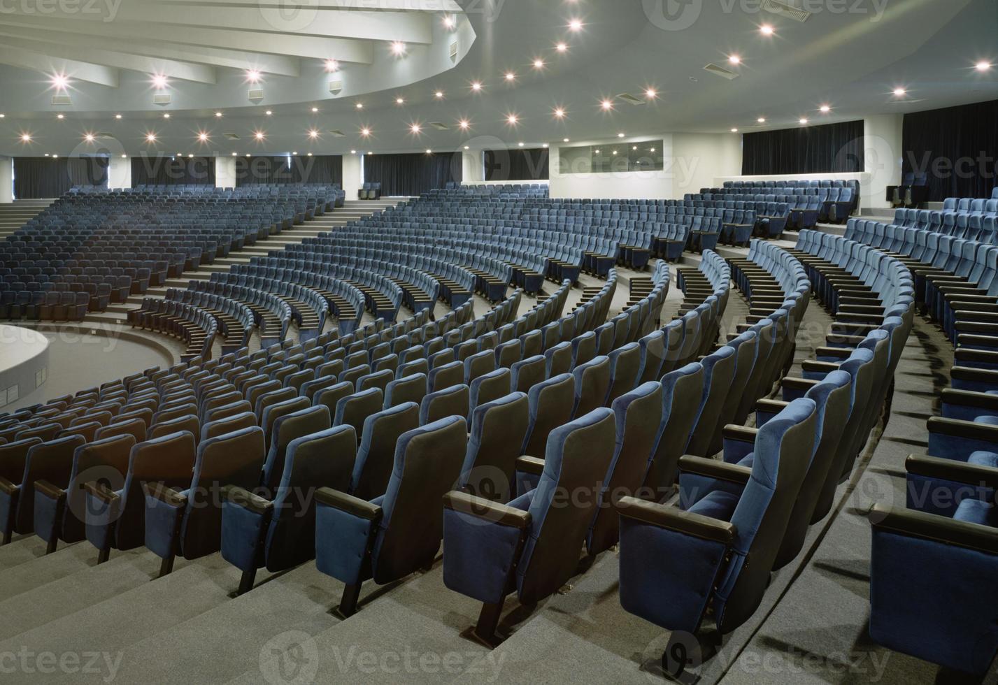 ett stort auditorium med flera rader med blå stolar foto