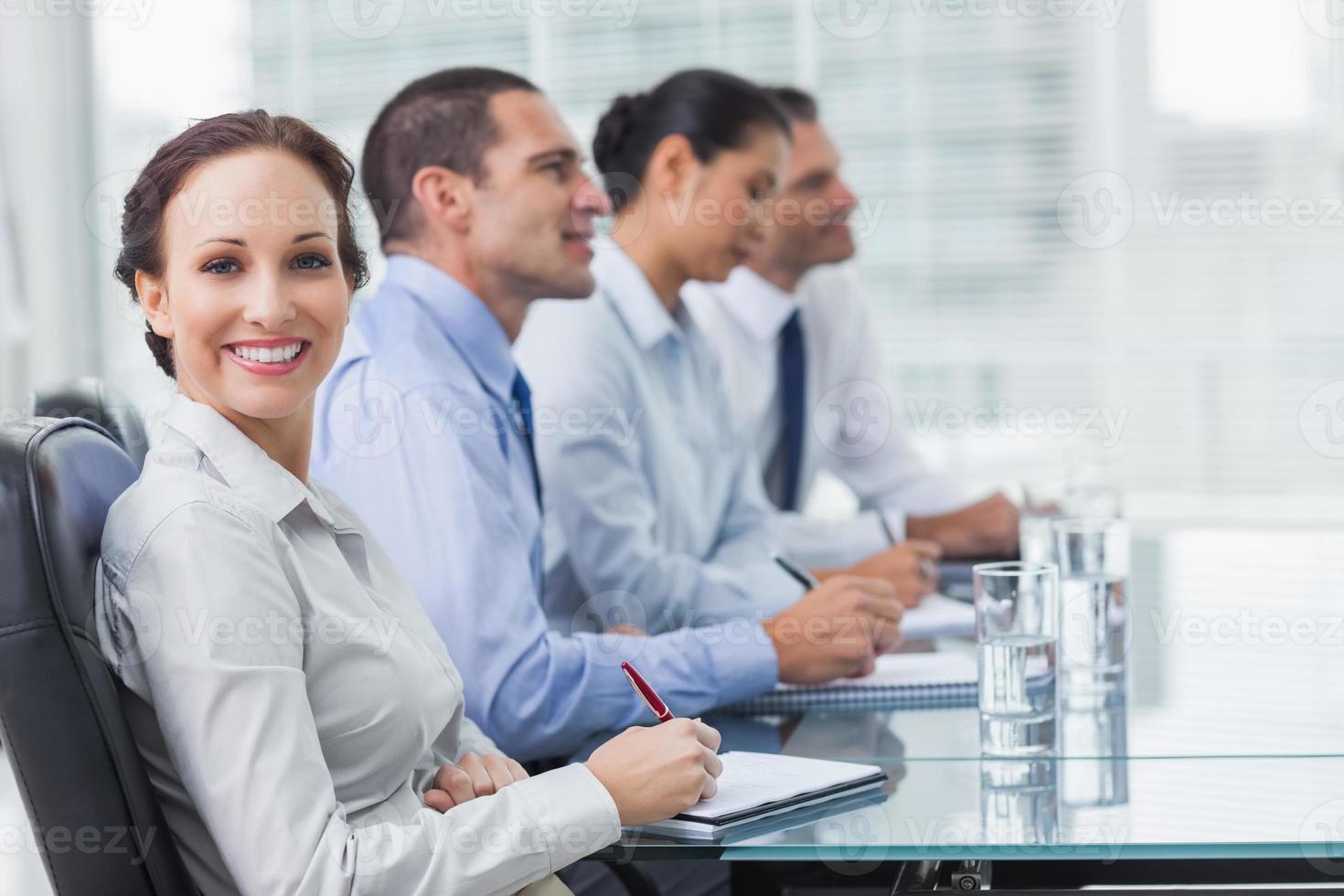 affärskvinna som ler mot kameran medan hennes kollegor lyssnar t foto