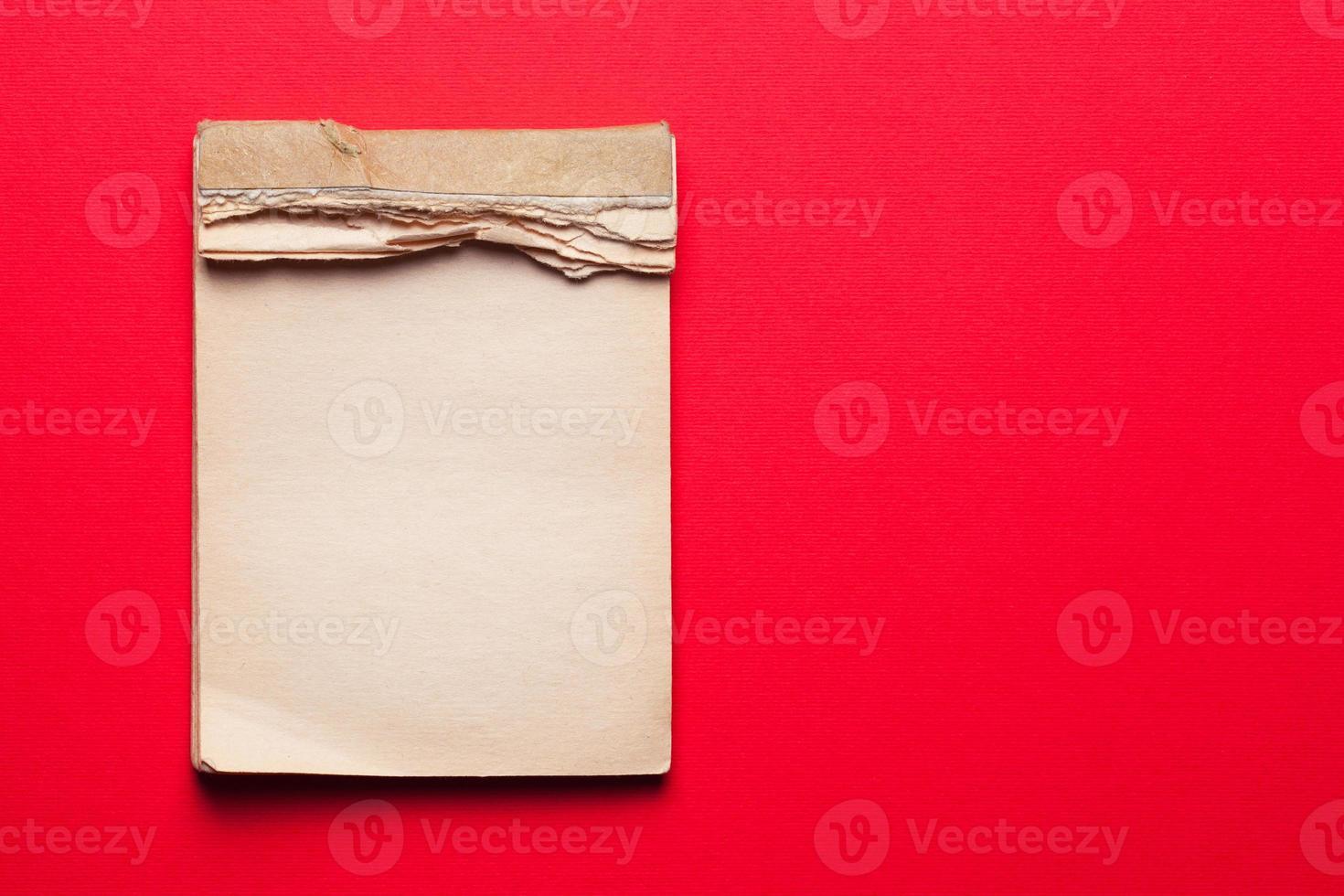 gammal anteckningsbok på röd bakgrund foto