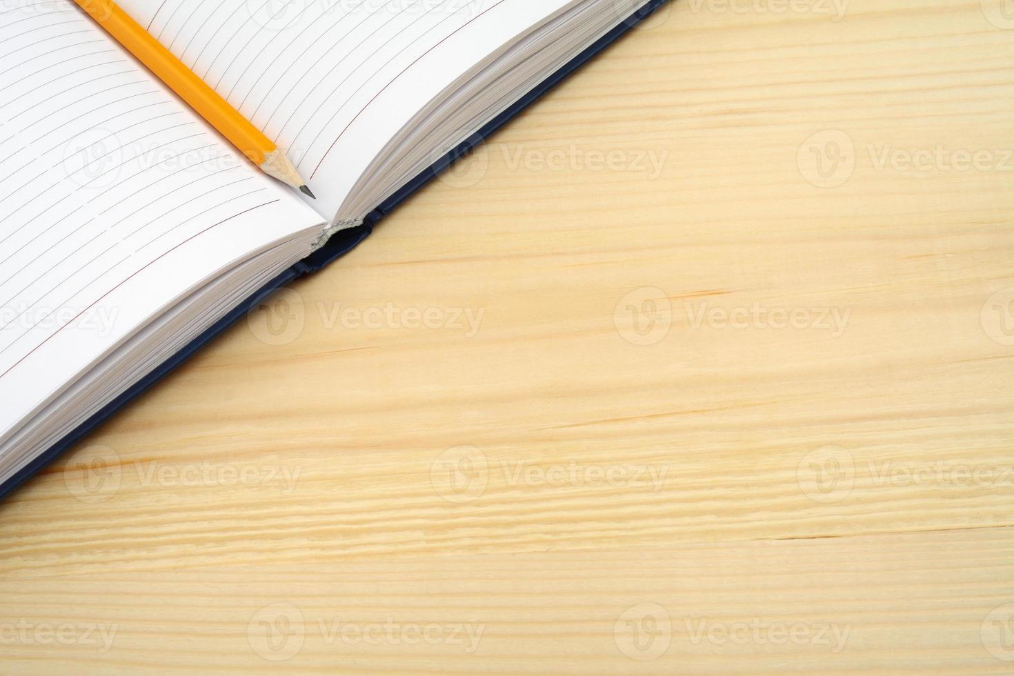 dagbok och penna på träbord med fri textutrymme. foto