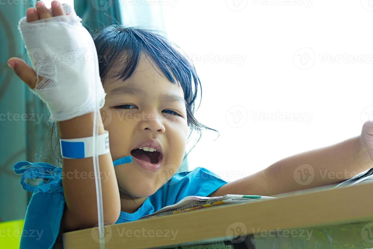 sjukdom asiatiska barn sitter på en stol på sjukhus foto