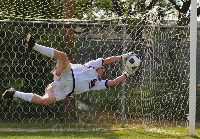 målvakt i luften och sparar en boll foto