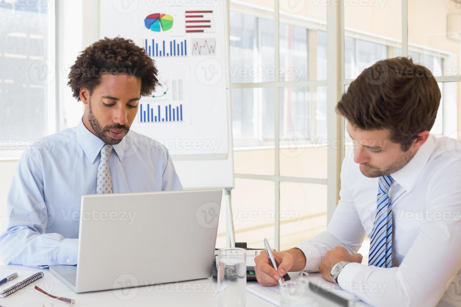 koncentrerade affärsmän med grafkort i bakgrunden foto