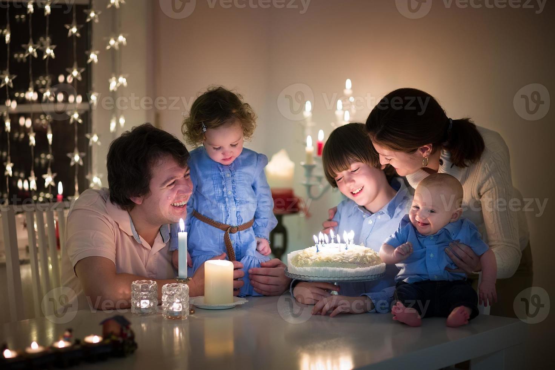ung familj med tre barn firar födelsedag för sin son foto