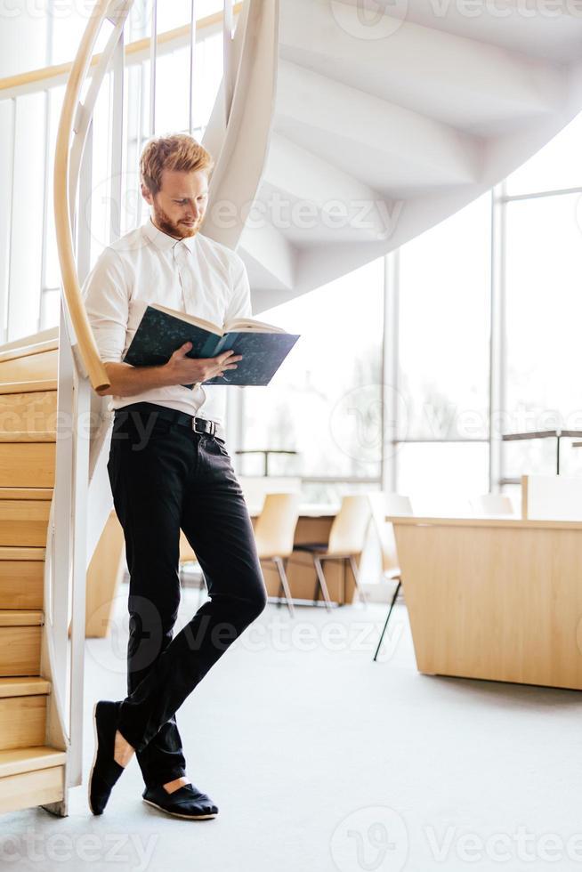 stilig intelligent kille som läser en bok i ett bibliotek foto