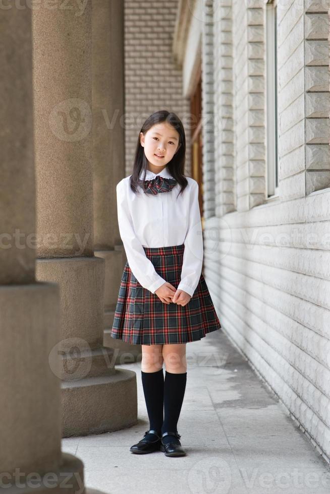 ung skolflicka poserar i skoluniform foto