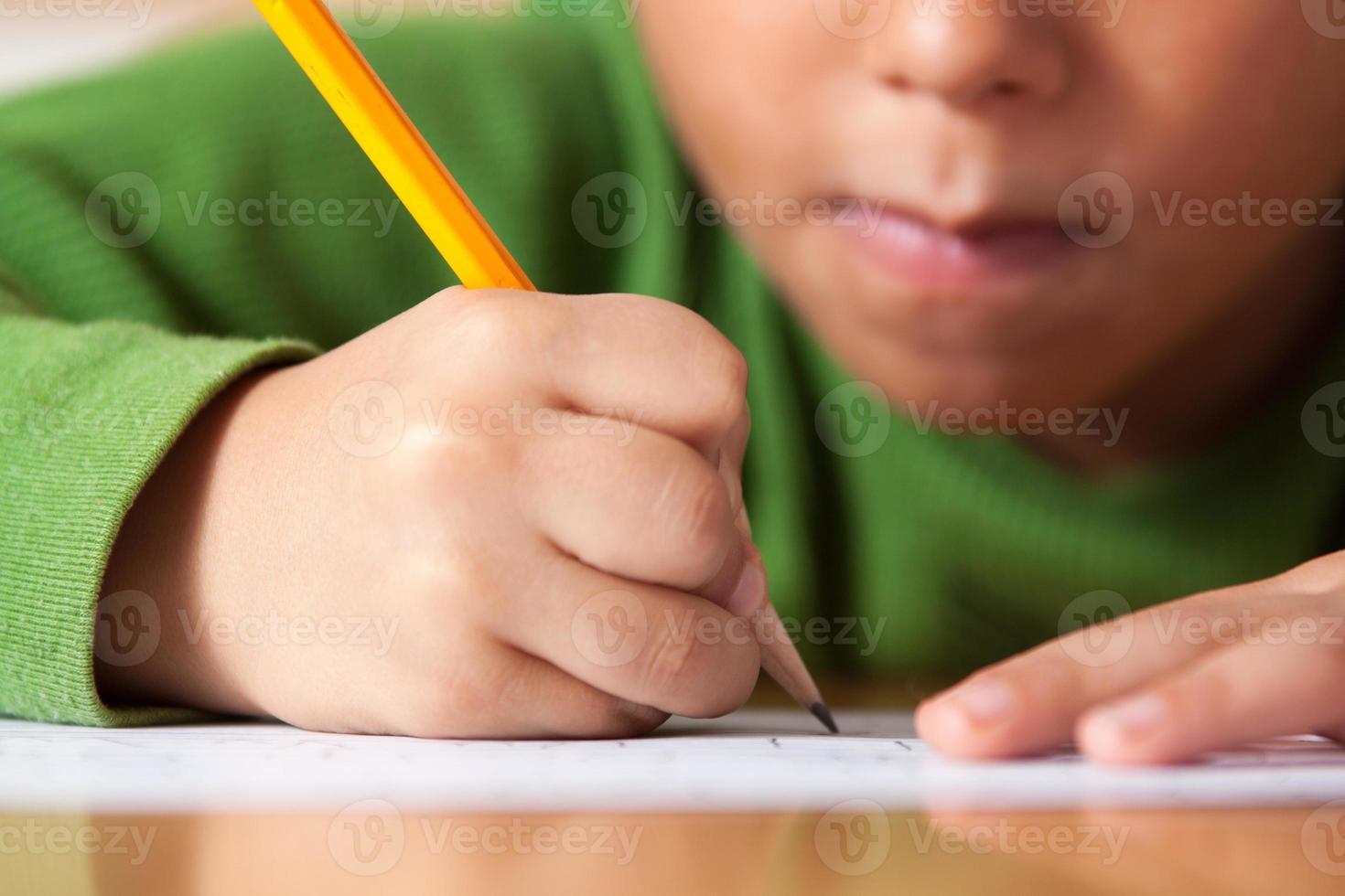 elementär pojke skriva foto
