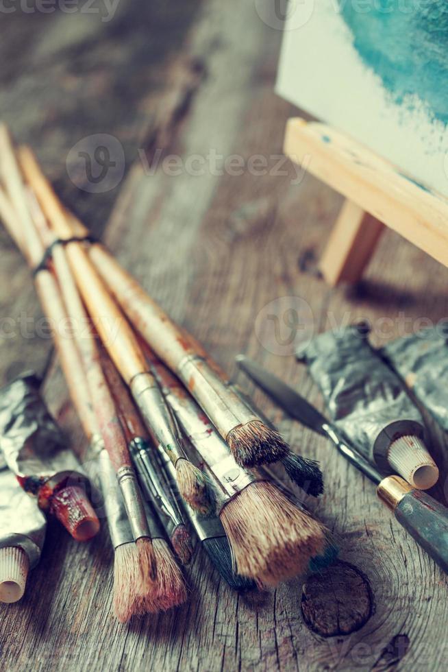 konstnärliga penslar, färgrör, palettkniv och staffli. foto