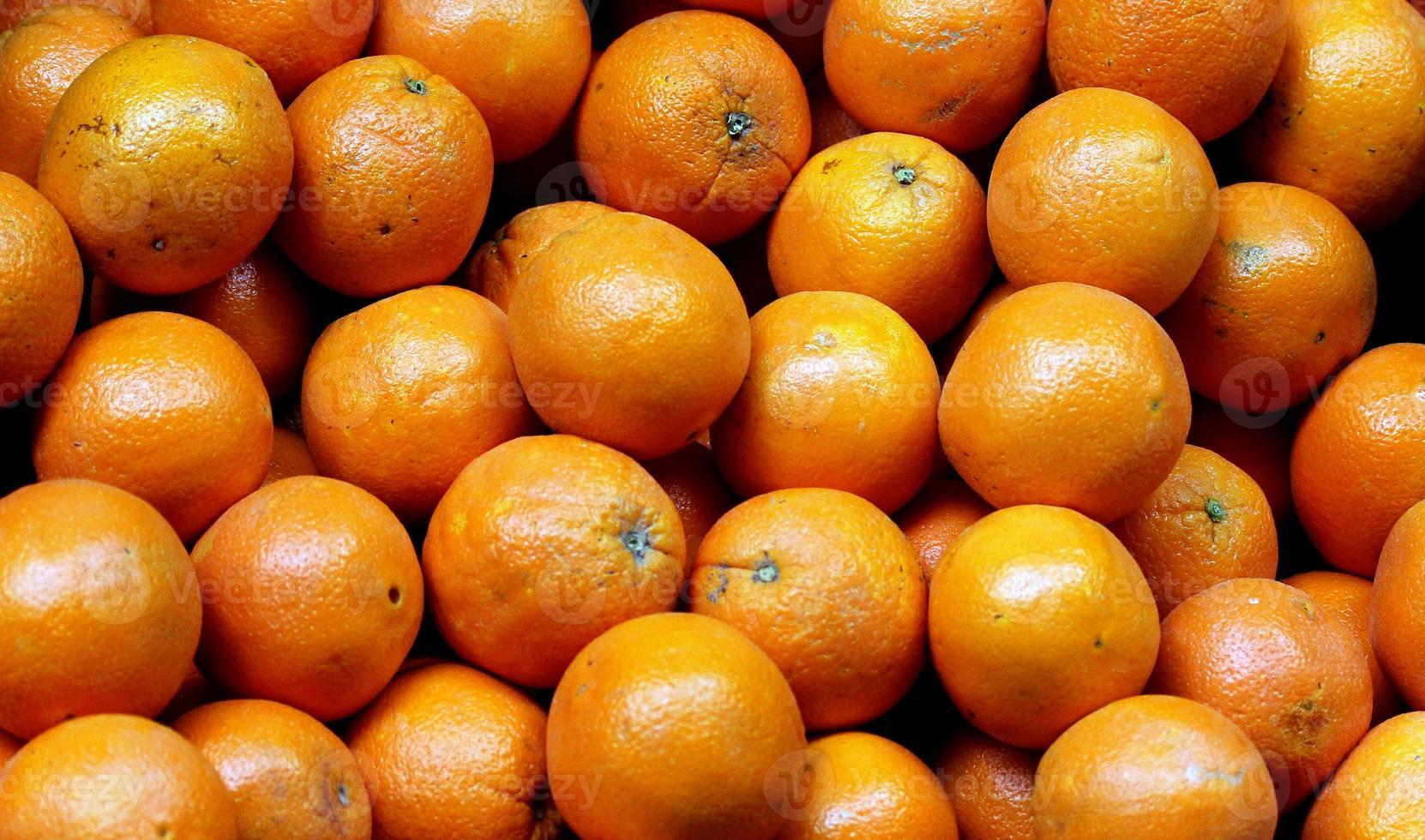 massa färska apelsiner på marknaden. selektiv inriktning foto