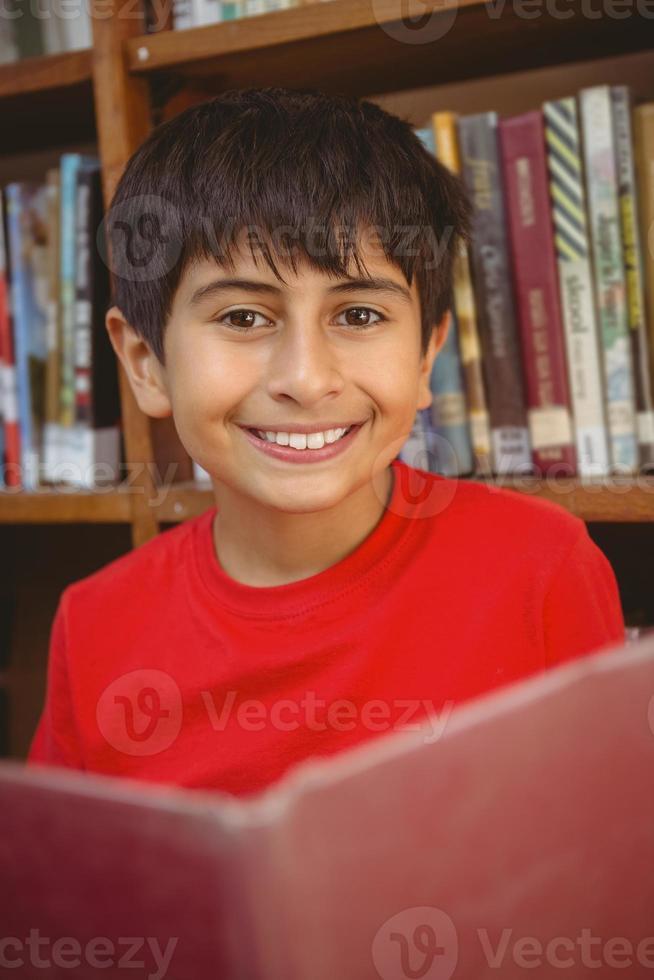 söt pojke som läser bok i biblioteket foto