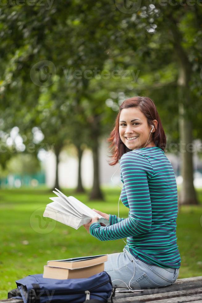 glad casual student sitter på bänkläsning foto