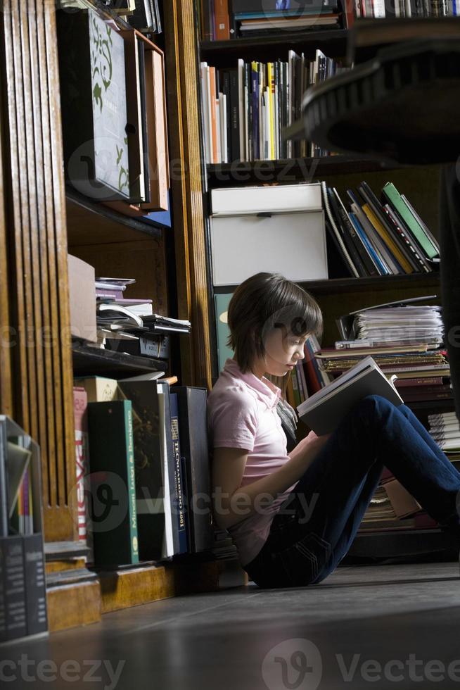 ung flicka läser bok i biblioteket foto