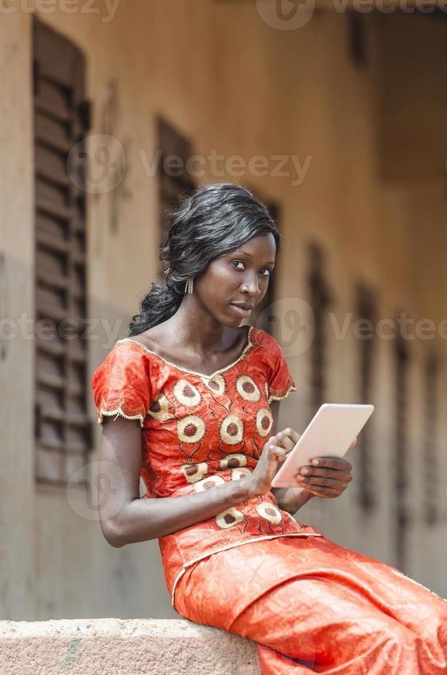 porträtt av afrikansk skolflicka som leker med sin surfplatta foto