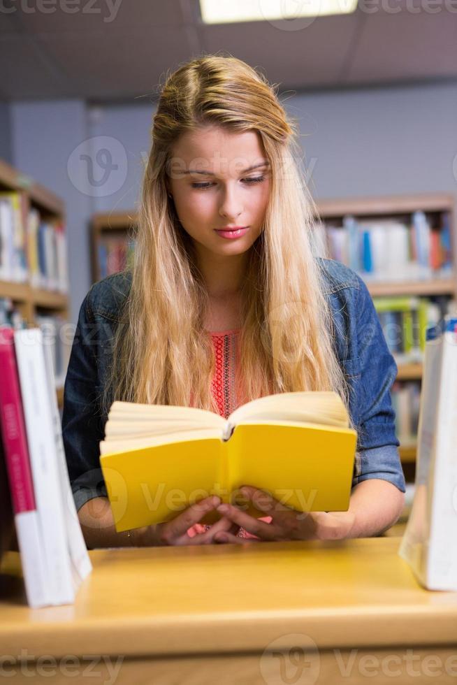 vacker student som studerar i biblioteket foto