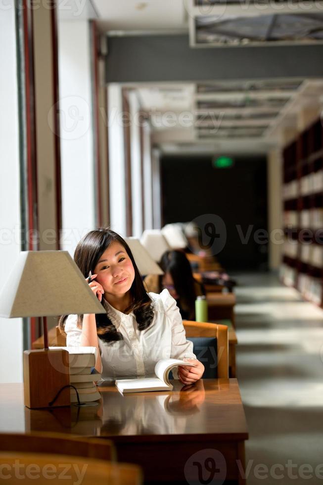 kvinna läser bok på biblioteket foto