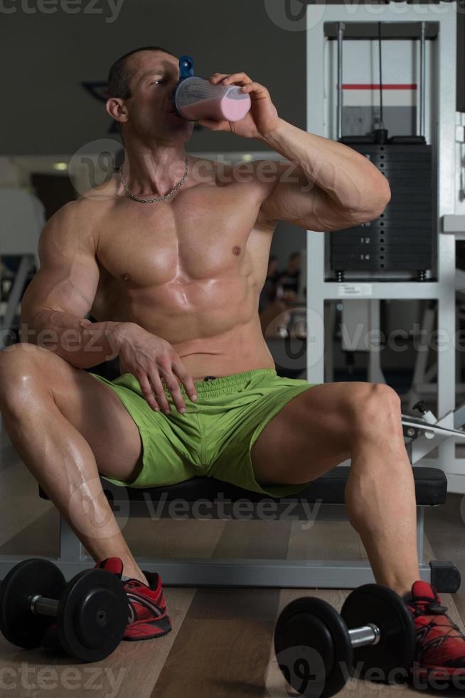 kroppsbyggare som dricker vassleprotein foto