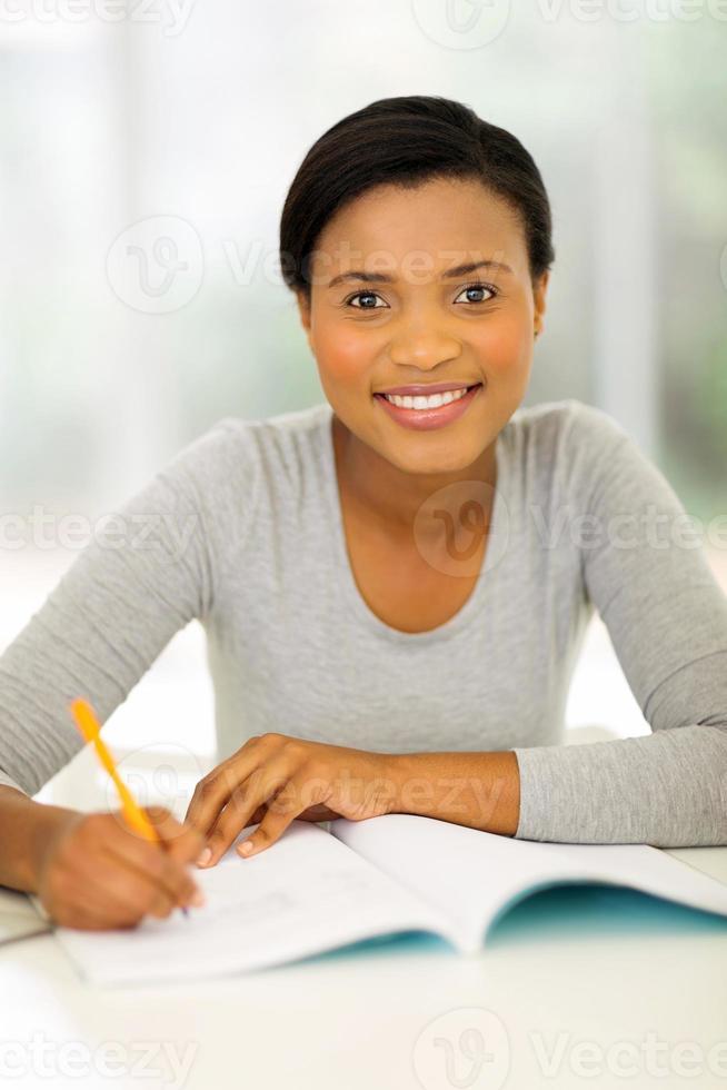 afrikansk högskolestudent som hemma studerar foto