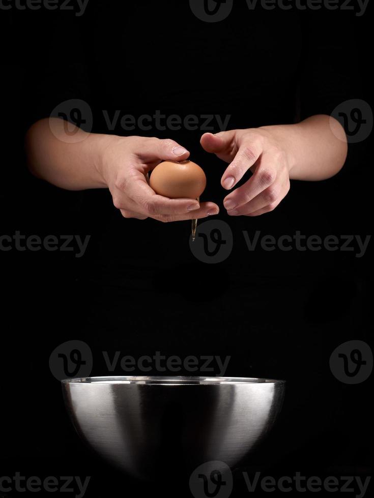 händer som bryter ett ägg foto
