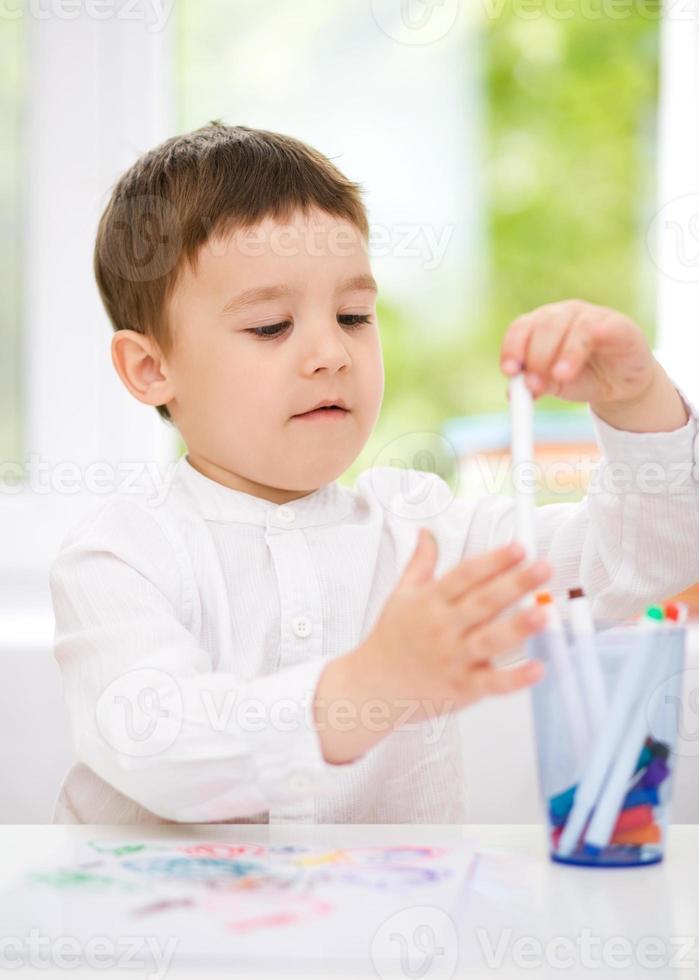 lilla pojken ritar på vitt papper foto